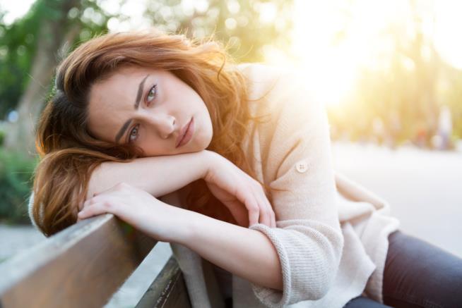 Una donna è seduta su una panchina con sguardo triste