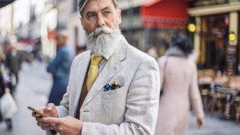 Primo piano di un bell'uomo maturo con giacca grigia e cravatta gialla