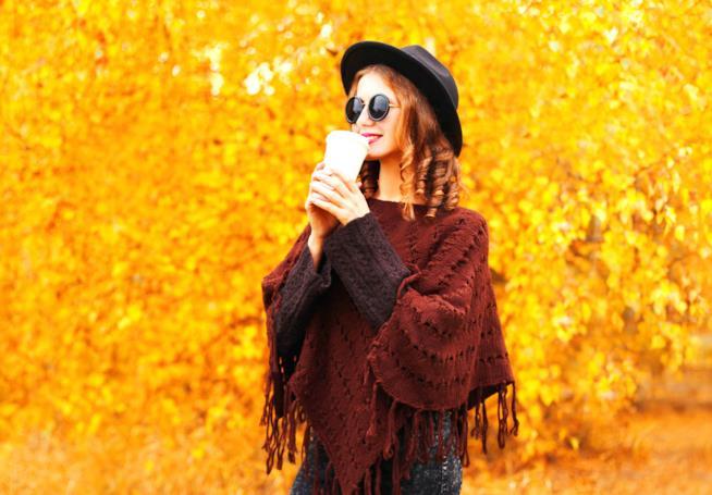 Una ragazza beve del caffè camminando in un parco autunnale