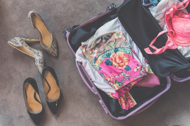 Valigia aperta con abiti e scarpe