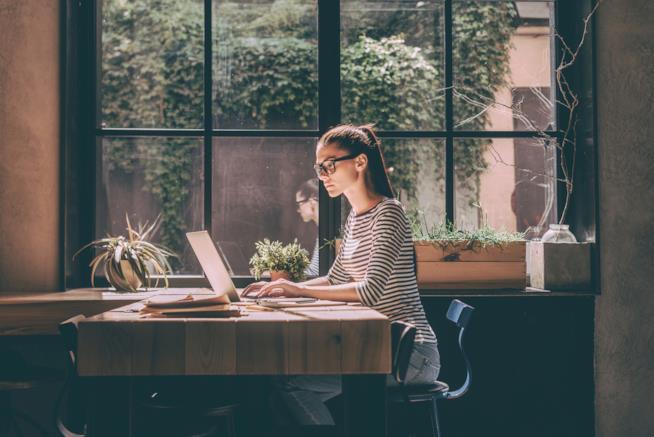 Una donna lavora al computer seduta davanti una scrivania