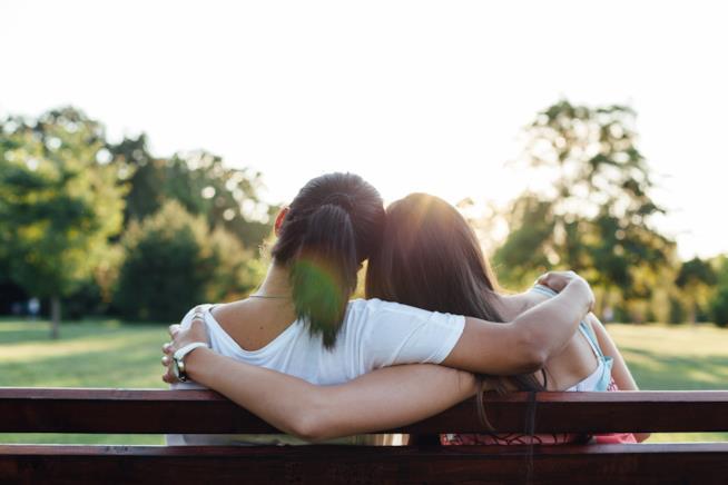 Due amiche sedute su una panchina abbracciate
