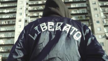 Liberato, di spalle, con una felpa co la scritta liberato, il cappuccio alzato e lo sfondo di un pal