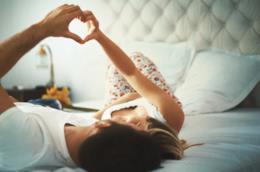 Un uomo e una donna sdraiati sul letto si guardano negli occhi