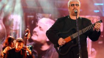 Pino Daniele, in nero, mentre suona la chitarra in piedi al microfono
