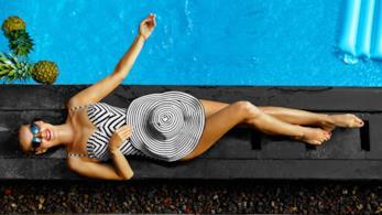 Una donna si rilassa a bordo piscina con costume e cappello abbinati