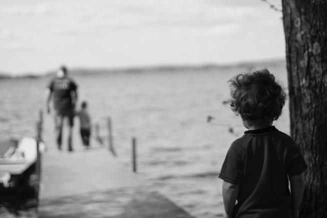 Bambino guarda il padre allontanarsi con un altro ragazzino