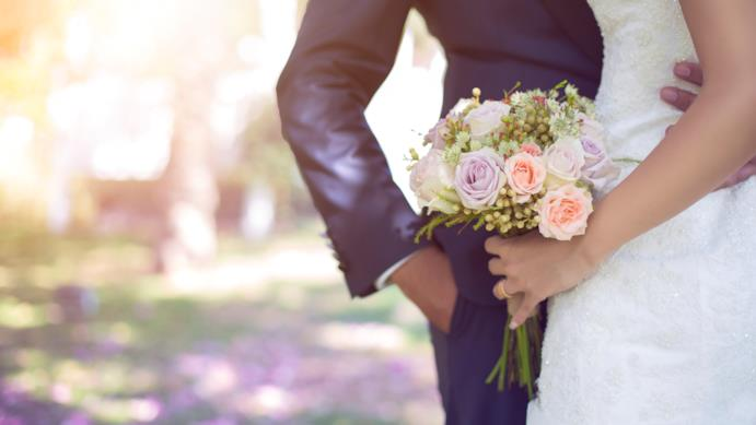 Uno sposo tiene la mano intorno alla vita della sposa