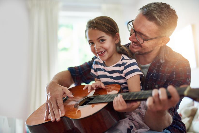 Padre e figlia suonano insieme la chitarra