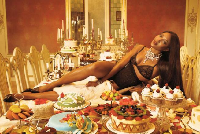 Naomi Campbell adagiata su un tavolo di cibo e dolci