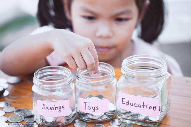 Una bambina con tre contenitori davanti.