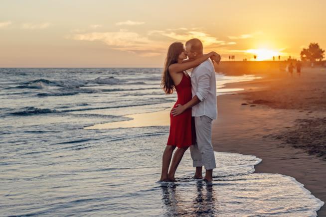 Coppia che si bacia sulla spiaggia al tramonto
