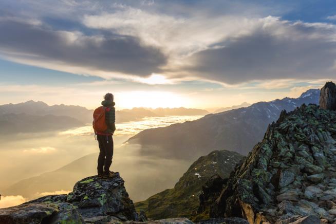 Un ragazzo guarda l'orizzonte mentre è sulla cima di una montagna