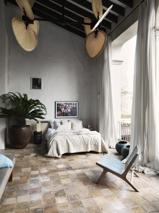 Camera da letto in stile jungle con lenzuola, coperte e tende in materiali naturali e colori neutri