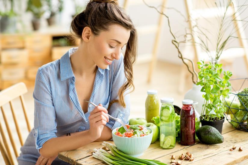 Ragazza seduta a tavola a mangiare un'insalata