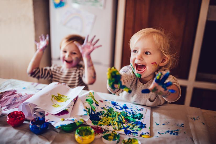 Bambini sporchi di pittura ma che ridono felici.