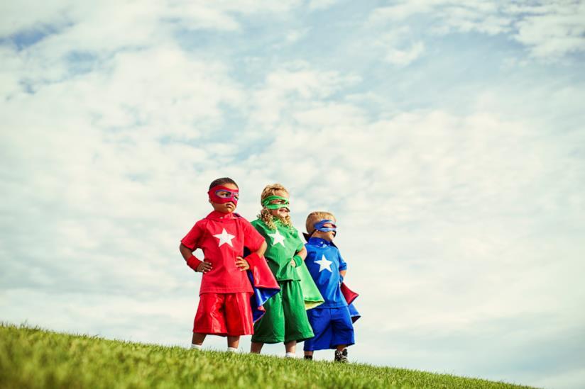 Tre bambini su una collina vestiti da supereroi