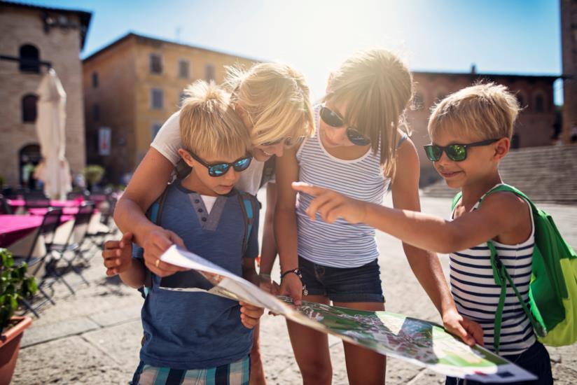 Dei bambini mentre tentano di leggere una mappa.