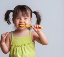 Bimba che gioca con lo spazzolino da denti