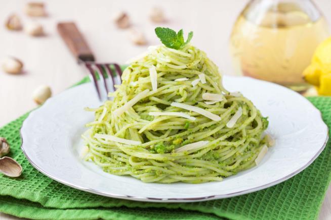 Primo piano di spaghetti con pesto di pistacchi e scaglie di parmigiano, serviti a forma di nido