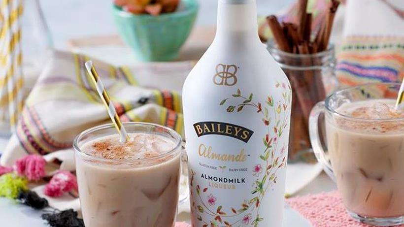 Una bottiglia di Baileys Almande ed un bicchiere con il liquore