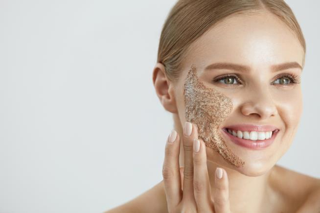 Ragazza con crema scrub esfoliante per il viso