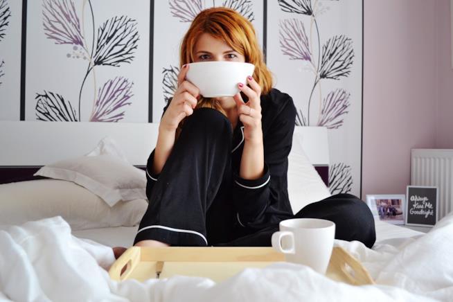 Ragazza a letto con una tazza di caffellatte