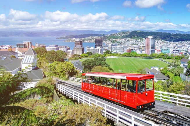 Un trenino rosso su dei binari viaggia verso la città