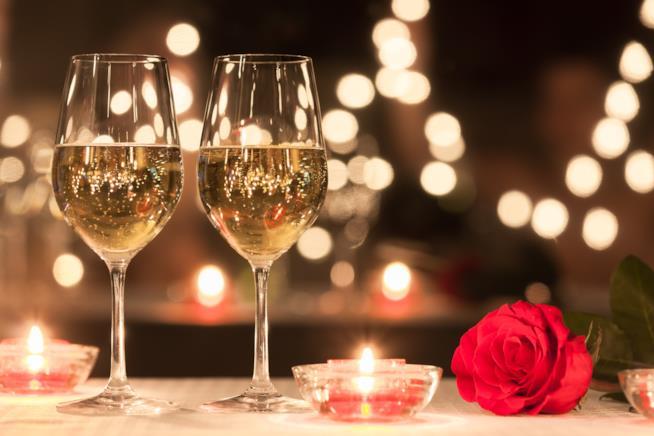 Calici di vino adagiati a tavola con una rosa rossa