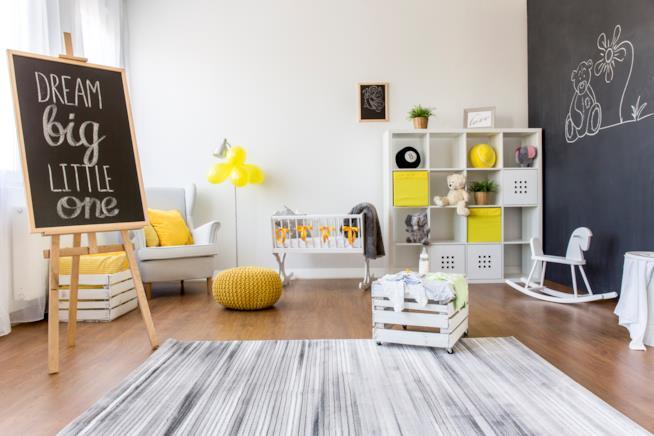 Cameretta con pareti e arredi bianchi, con una parete verniciata lavagna e accessori in giallo