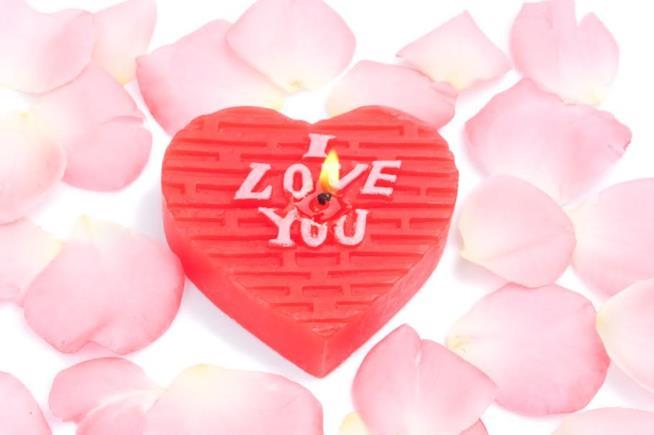 Una candela con petali di rosa