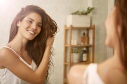 Una donna che si guarda allo specchio mentre si tocca i capelli.