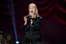 Christina Aguilera, in nero, su sfondo rosso, canta in piedi al microfono