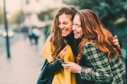 Due amiche abbracciate sorridono allegre abbracciandosi