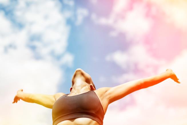 Una ragazza guarda verso il cielo a braccia aperte