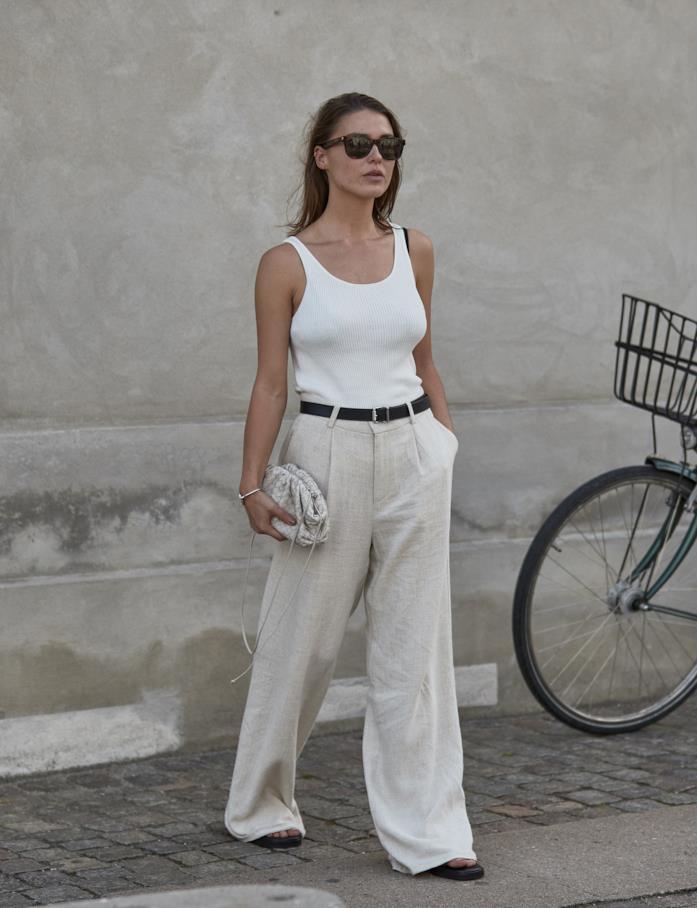 Canotta bianca abbinata a pantaloni larghi di lino e scarpe flat