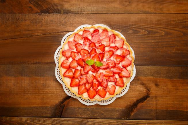 Crostata di fragole e crema pasticcera adagiata su centrino bianco