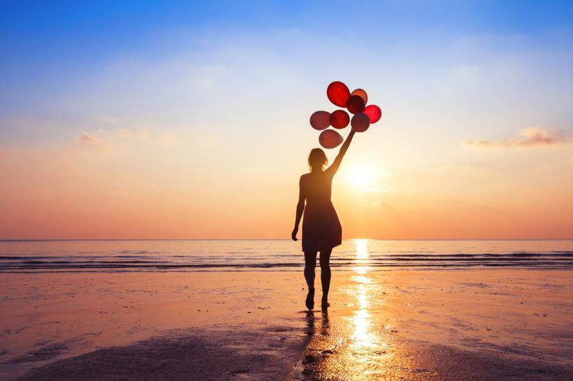 Ragazza in riva al mare con dei palloncini
