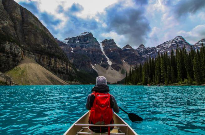 Ragazza di spalle in canoa su un lago in Canada