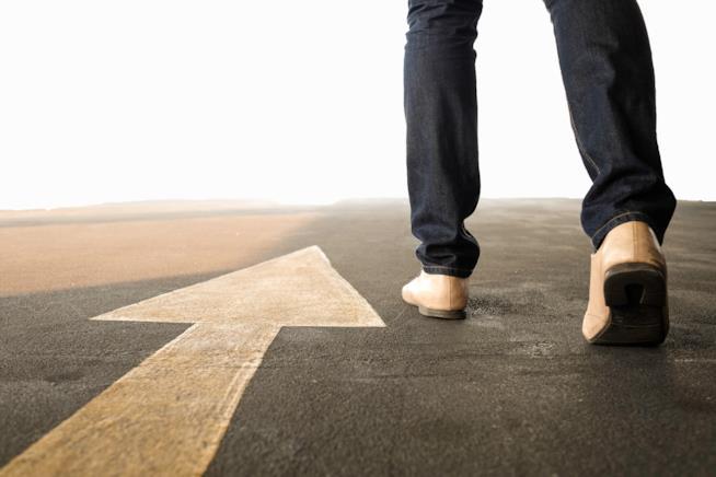 Una strada con una freccia direzionale disegnata con in primo piano i piedi di un uomo