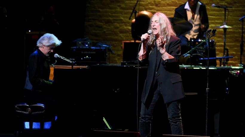 Patti Smith, vestita di nero, canta al microfono, accompagnata da un pianista