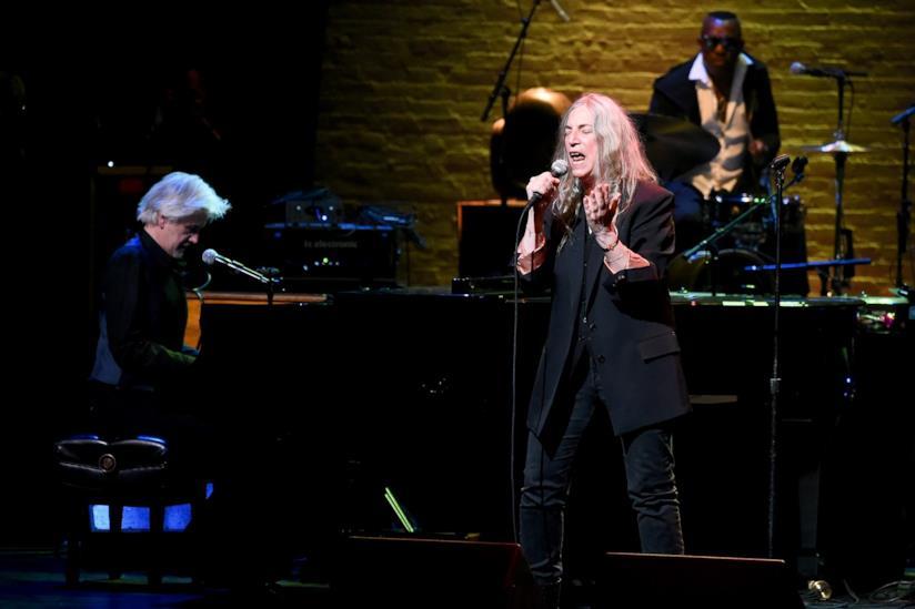Patti Smith, vestita di nero, canta al microfono, accompagnata da un pianista