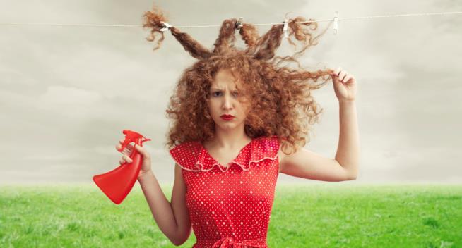 Ragazza riccia con in mano uno spruzzino si tiene una ciocca di capelli con espressione corrucciata