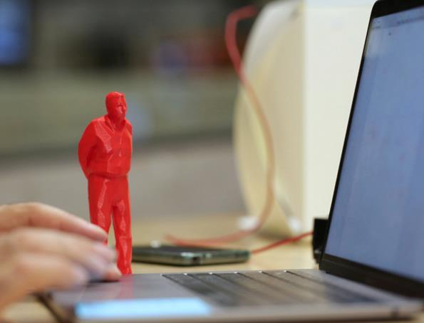 Statuetta rossa di un uomo in miniatura, vicino a un computer