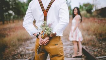 Un uomo di spalle con un mazzo di fiori in mano.