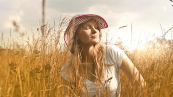 Ragazza seduta in un campo prende il sole