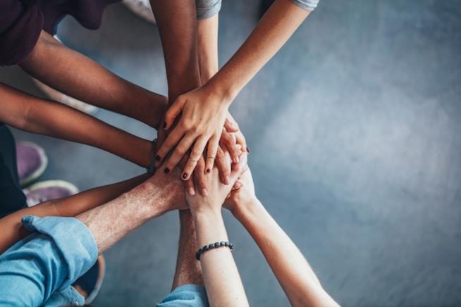 Particolare di mani disposte l'una sull'altra in segno di unione