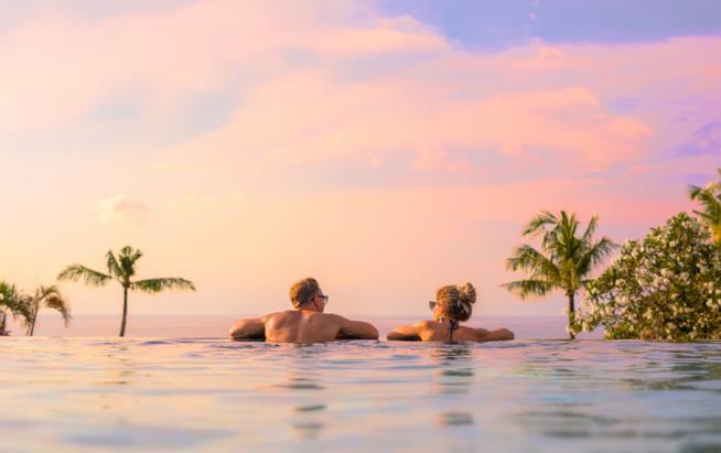Coppia in relax in piscina di un hotel di lusso