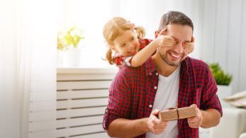 Una bambina spunta alle spalle del padre che ha un suo regalo