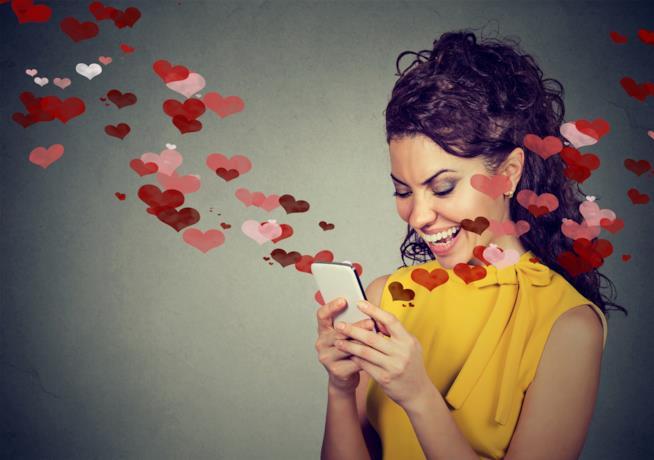 Una donna chatta con una serie di cuori che escono dallo schermo